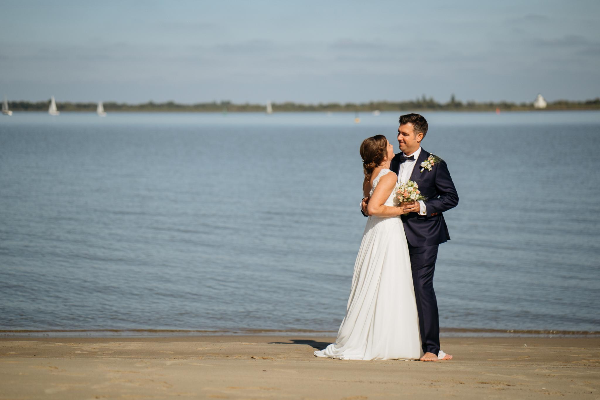 Lachendes Brautpaar am Strand